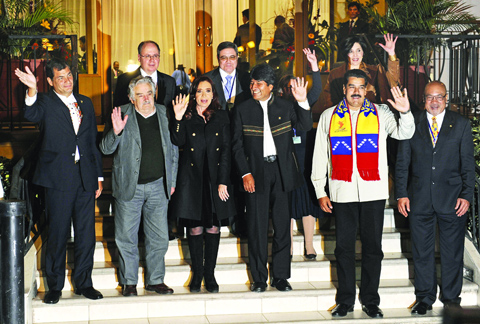 (L-R, front row) Presidents Rafael Correa of Ecuador, Jose Mujica of Uruguay, Cristina Fernandez de Kirchner of Argentina, Evo Morales of Bolivia, Nicolas Maduro of Venezuela and Desi Bouterse of Suriname pose for pictures after a meeting called after Evo Morales' plane was rerouted amid suspicions US fugitive Edward Snowden was aboard, in the Bolivian central city of Cochabamba, on July 4, 2013. Leftist Latin American leaders gathered in Cochabamba on Thursday to back President Evo Morales, fuming after some European nations temporarily refused his plane access to their airspace amid suspicions US fugitive Edward Snowden was aboard. Snowden is seeking sanctuary in several nations to evade US espionage charges.   AFP PHOTO / JORGE BERNAL