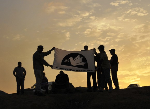 The sun sets behind members of Veterans For Peace as they conclude their visit to Al-Araqeeb. Photo by ELLEN DAVIDSON