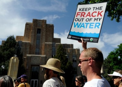 Adam Stenftenagel, right, holds an anti-fracking sign outside the Boulder County Courthouse on June 18, 2013, before a county commissioners' meeting regarding a fracking moratorium. (Jeremy Papasso / Daily Camera)
