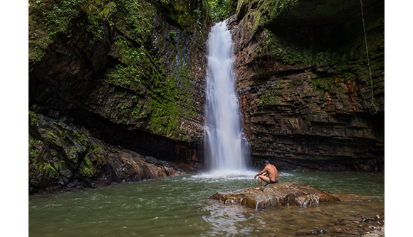 Shuar leader Patricio Tiwiram sits below a waterfall along the Rio Kupiamias. This is a sacred spot for the Shuar and one threatened by nearby mining concessions.