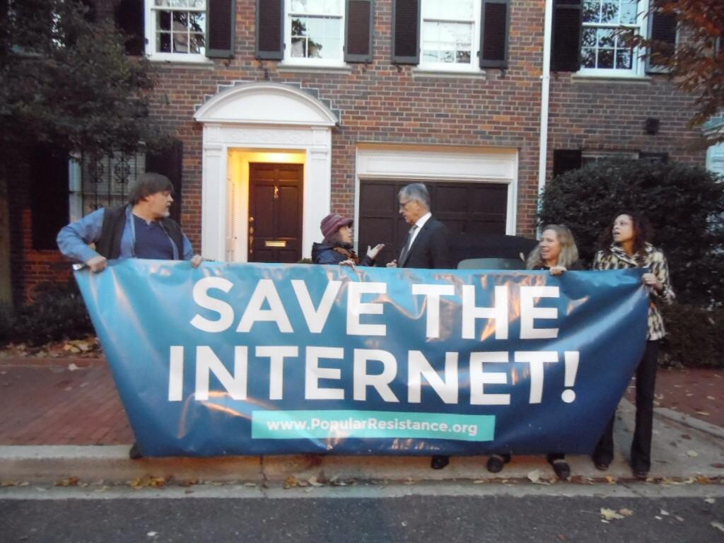 Activists speak with FCC Chairman Tom Wheeler as they blockade his driveway in Georgetown this morning.