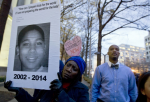 Tomiko Shine holds up a picture of Tamir Rice, the 12 year old boy fatally shot on Nov. 22 by a rookie police officer, Monday, Dec. 1, 2014. (AP Photo/Jose Luis Magana)