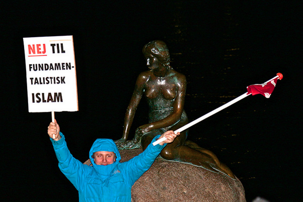 """An enthusiastic PEGIDAdk supporter waves the Danish flag and a """"No to fundamentalist Islam"""" sign in front of the Little Mermaid statue. (Photo: Linda Pershing)"""