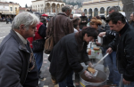 Soup kitchen volunteers serve food in Athens. Photograph: Lefteris Pitarakis/AP