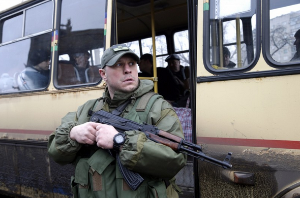 A Ukrainian soldier holds a weapon as people wait on a bus to leave the town of Debaltseve in Artemivsk, Ukraine, Tuesday, Feb. 3, 2015. Since the unrest in eastern Ukraine surged anew in early January, the separatists have made notable strides in clawing territory away from the government in Kiev. Their main offensive is now directed at Debaltseve — a government-held railway junction once populated by 25,000 people that lies between the rebel-held cities of Luhansk and Donetsk. Almost 2,000 residents have fled in the last few days alone. (AP Photo/Petr David Josek)