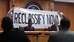 Advocates hold Reclassify Now banner behind FCC commissioners at a public meeting. Commissioners Clyburn and Wheeler can be seen.