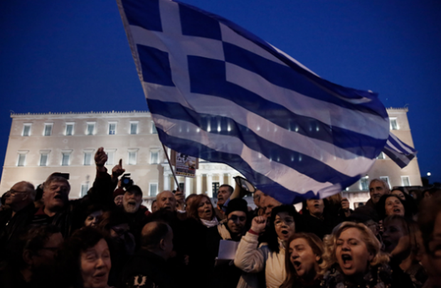 Protesters wave Greek flags in front of Greece's Parliament to support the new Syriza-led government in its eurozone bailout negotiations last month. (AP / Petros Giannakouris)