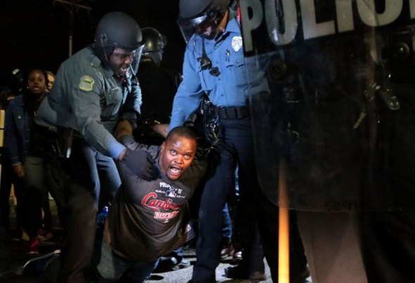 Police in riot gear arrest Charles Brooks of Pine Lawn in front of the Ferguson Police Station on Wednesday, March 11, 2015. About 150 demonstrators gathered outside the police department demanding the dismantling of the Ferguson Police Department and resignation of Mayor James Knowles III. Earlier in the day Ferguson Police Chief Tom Jackson turned in his resignation. Photo by Laurie Skrivan, lskrivan@post-dispatch.com