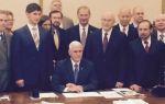 "Gov. Mike Pence (R) signing Indiana's ""Religious Freedom Restoration Act"" while surrounded by anti-LGBT activists. CREDIT: TWITTER/MICAH CLARK"