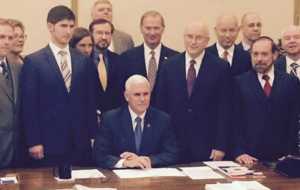 """Gov. Mike Pence (R) signing Indiana's """"Religious Freedom Restoration Act"""" while surrounded by anti-LGBT activists. CREDIT: TWITTER/MICAH CLARK"""