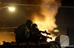 Police watch over protests which erupted after the police killing of Michael Brown, Monday, Nov. 24, 2014, in Ferguson, Mo.