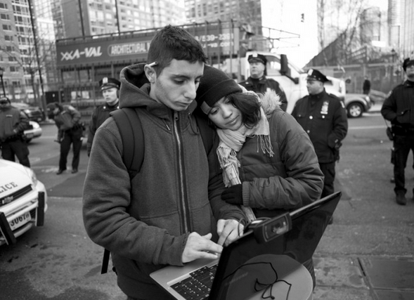 A pair of citizen journalists stand close together as one types on a laptop in front of a row of police officers at an Occupy Wall Street protest on December 12, 2011. In revolutionary media, citizen journalists no longer try to remain neutral or removed from the action happening in the streets. (Flickr / Jessica Lehrman)
