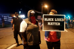 A woman holds up a sign reading Black Lives Matter in the street in Ferguson, Missouri, on the anniversary of Michael Brown's death. Photograph: Jim Vondruska/Xinhua Press/Corbis