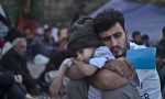 A Syrian refugee child sleeps on his father's arms. Photograph by Muhammed Muheisen for AP