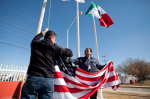 Workers at one of the maquiladoras in Juarez, Mexico, raise flags in 2013. Under the North American Free Trade Agreement, such factories have proliferated, but critics of the pact say its effects have been economically devastating on both sides of the U.S.-Mexico border.  (Ivan Pierre Aguirre / AP)