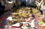 Afghan villagers sit near the bodies of children who they said were killed during a NATO air strike in the Kunar province of Afghanistan. April 7, 2013. (Reuters)