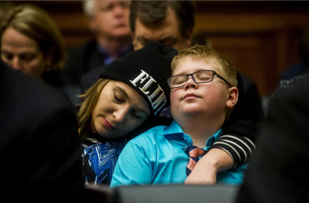 Flint resident Desiree Duell rests her head on the shoulder of her son David Henderson during the Flint hearing. Photograph: Jake May/AP