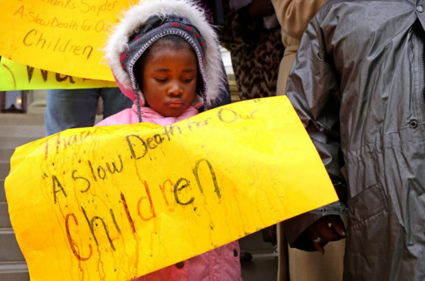 Makayla Terry, 3, looks down at her sign as rain has damaged during a protest on the current Flint water hazard on the steps of the State Capitol in Lansing Wednesday, October 28, 2015. (Danielle Duval | MLive.com)