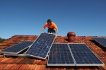 Solar system installer Thomas Bywater adjusts new solar panels on the roof of a house in Sydney, August 19, 2009. REUTERS/Tim Wimborne