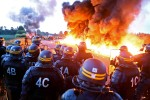 Riot police stand guard behind a fire as refinery workers hold a blockade of the oil depot of Douchy-Les-Mines to protest against the government's proposed labour reforms, on May 25. Photographer: Francois Lo Presti/AFP via Getty Images