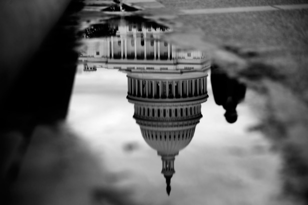 The U.S. Capitol is reflected in a puddle next to the Capitol Reflecting Pool in Washington, D.C., Oct. 15, 2013. Photo: Andrew Harrer/Bloomberg/Getty Images