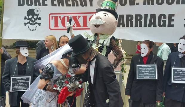 "Duke Energy protesters posing as Gov. Pat McCrory and CEO Lynn Good seal ""toxic marriage"" with a kiss. T. Ortega Gaines"