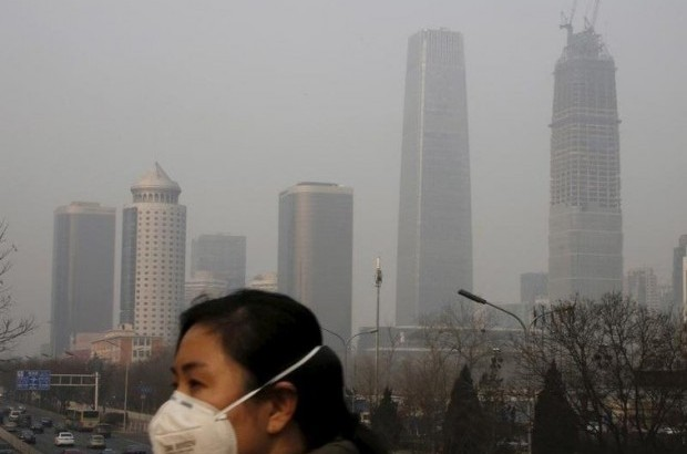 A woman wearing a protective mask makes her way in a business district on a heavily polluted day in Beijing