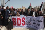 Palestinian fishermen hold banners in a protest to demand the boycott of the Israeli agricultural products, during the 10th annual Israeli Apartheid Week