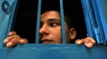 A boy looks on from his one-man cell at a juvenile prison. (AP/Muhammed Muheisen)