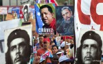 """People hold up images showing Fidel Castro, second from right, Venezuela's late President Hugo Chavez, center, and Cuba's revolutionary hero Ernesto 'Che' Guevara, bottom left and right, during a May Day march in Revolution Square in Havana, Cuba, Wednesday, May 1, 2013. The image of Chavez carries the words in Spanish """"Chavez : Our best friend."""" (AP Photo/Ramon Espinosa)"""