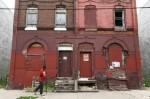 A man walks through a blighted neighborhood, July 11, 2013, in Philadelphia. (Credit: AP/Matt Rourke)