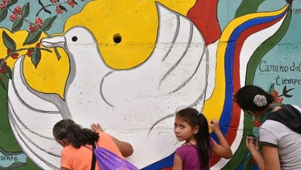 A peace mural is painted near the road leading to Planadas, Colombia, where a peasant uprising in 1964 led to the birth of the FARC. | Photo: AFP