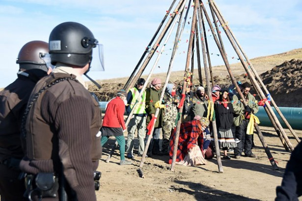 Gathered under tipi poles at the protest site in Standing Rock, a group of water protectors continue their demonstration after being told to leave by the police on October 10, 2016. (Photo: Ellen Davidson)