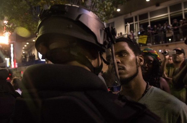 NICHOLAS KAMM VIA GETTY IMAGES A protester stares at riot police during a demonstration against police brutality in Charlotte.