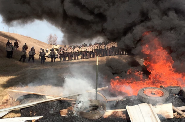 Tires burn as armed soldiers and law enforcement officers stand in formation to force out Dakota access pipeline protesters. Photograph: Mike McCleary/AP