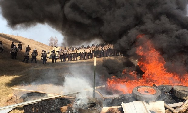 Tires burn as soldiers and law enforcement officers stand in formation to force Dakota Access pipeline protesters off private land. Photograph: Mike McCleary/AP
