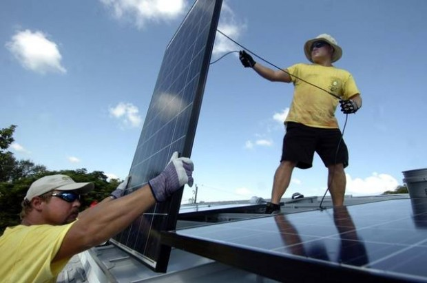 In this file photo, workmen install install a solar panel array for a whole-house solar power source at a home in Pinecrest. TIM CHAPMAN MIAMI HERALD STAFF