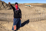 A masked warrior woman raises her fist at a Dakota Access construction site./Photo by Doug Grandt