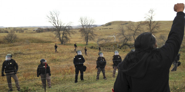 AP Photo/James MacPherson A Dakota Access pipeline protester defies law enforcement officers who are trying to force them from a camp on private land in the path of pipeline construction, Thursday, Oct. 27, 2016 near Cannon Ball, ND. Soldiers and law enforcement officers dressed in riot gear began arresting protesters who had set up a camp on private land to block construction of the Dakota Access oil pipeline.