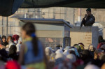 An Israeli border police officer stands as Palestinian women wait to cross the Qalandia checkpoint between the West Bank city of Ramallah and Jerusalem, June 17, 2015. (AP Photo/Majdi Mohammed)