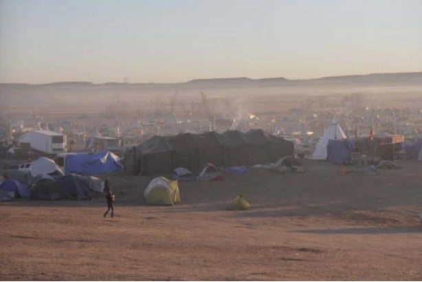 The sun rises over Oceti Sakowin Camp just north of the Cannonball River where 2,000 opponents of the Dakota Access Pipeline have been living. Opponents began arriving in small numbers in April. Larger numbers came in July and August, and more continue to arrive every day. Lynette Wilson/Episcopal News Service