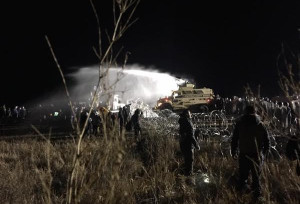 Twitter/Clayton Thomas Mueller Water protectors stand off against militarized police who doused them in water cannons in 20-degree temperatures. Read more at http://indiancountrytodaymedianetwork.com/2016/11/21/mainstream-media-mia-dapl-action-met-water-cannons-and-mace-166527