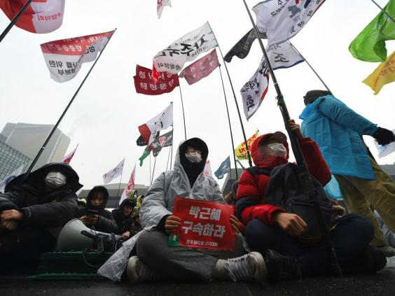 Protesters sit on the street during an anti-government rally demanding the resignation of South Korea's President Park Geun-Hye (AFP)