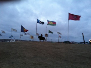 A lone rider at dusk between flags of Native nations.