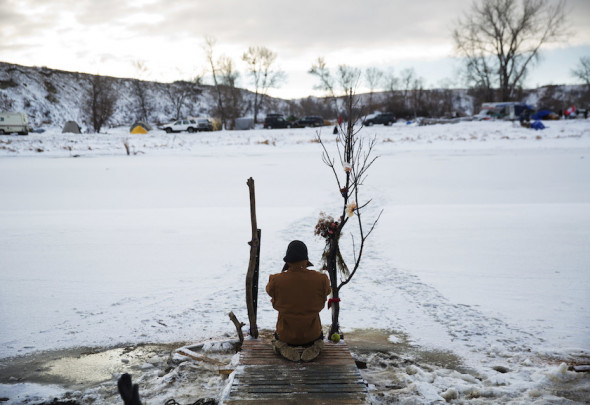 Army veteran Nick Biernacki, of Indiana, prays at the Cannonball River at the Oceti Sakowin camp where people have gathered to protest the Dakota Access oil pipeline in Cannon Ball, N.D., Sunday, Dec. 4, 2016. AP Photo by David Goldman