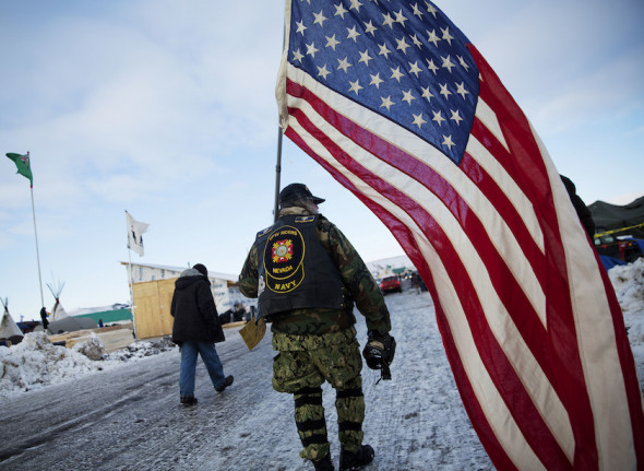 Navy veteran Rob McHaney, of Reno, N.V., walks with an American flag at the Oceti Sakowin camp where people have gathered to protest the Dakota Access oil pipeline in Cannon Ball, N.D., Sunday, Dec. 4, 2016. AP Photo by David Goldman