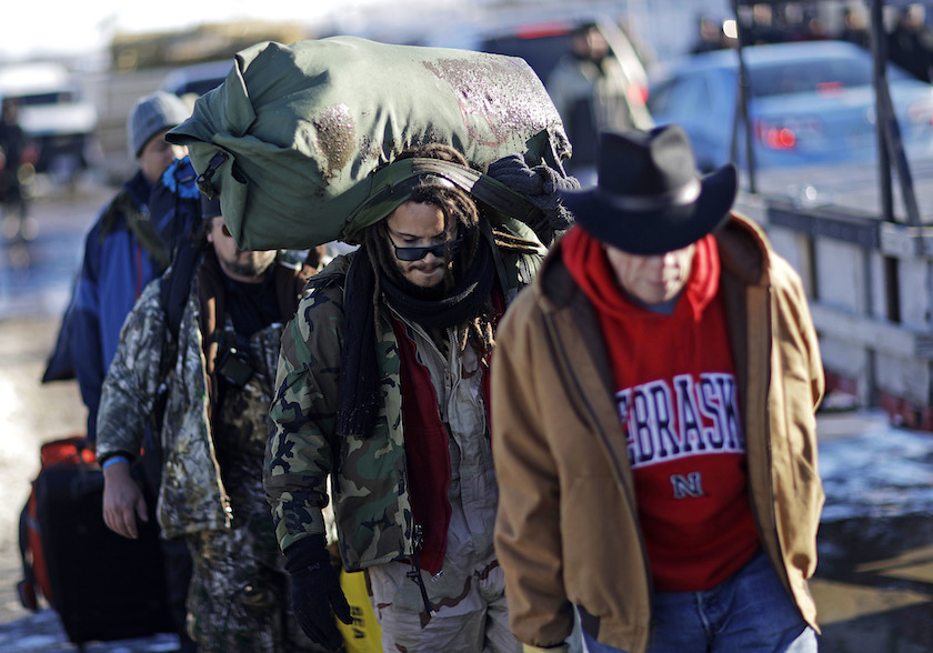 Marine Corps veteran Nesky Hernandez, center, carries his pack after arriving with fellow veterans at the Oceti Sakowin camp where people have gathered to protest the Dakota Access oil pipeline in Cannon Ball, N.D., Sunday, Dec. 4, 2016. AP Photo by David Goldman