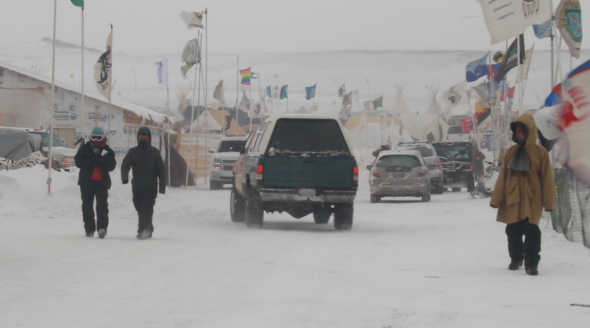 Cars drive through the Standing Rock camp during a snow blizzard. Task & Purpose photo