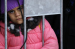 A migrant girl looks through the fence waiting to register with the police in refugee center in the southern Serbian town of Presevo, in Belgrade, Serbia, Friday, Nov. 13, 2015. CREDIT: AP PHOTO/DARKO VOJINOVIC