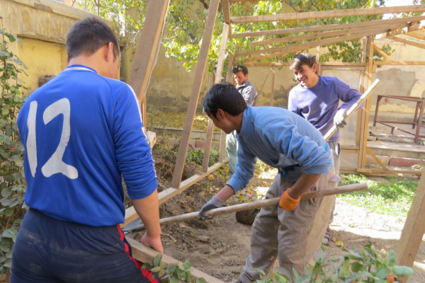 It was a year of grief for Ali ( extreme right and smiling ), as he had lost his older brother who was a soldier killed in the war raging across Afghanistan. Here, Ali and other Afghan Peace Volunteer community members install a greenhouse before winter set in.